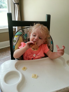 Eating dad's peanut butter and jelly sandwich.